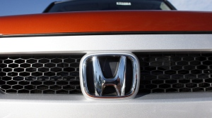 The company logo shines on a new Honda vehicle on Sunday, Nov. 1, 2009.