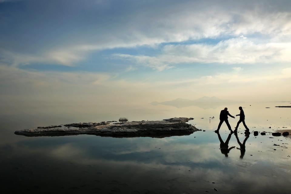 Two men walk toward salt-covered rocks that were once deep underwater at Lake Oroumieh, in northwestern Iran, Saturday, Feb. 15, 2014. (AP / Ebrahim Noroozi)
