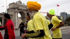One-hundred-year-old Fauja Singh (centre) takes part in the Toronto Waterfront marathon on Sunday, Oct. 16, 2011. (Chris Young / THE CANADIAN PRESS)