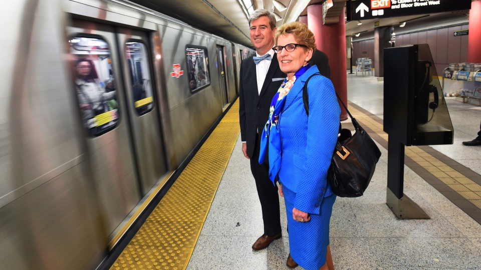 Ontario Premier Kathleen Wynne, right, and Glen Murray, Minister of Infrastructure, wait to board the subway while en route to Wynne's speech at the Toronto Region Board of Trade in Toronto Monday, April 14, 2014. (Darren Calabrese / THE CANADIAN PRESS)