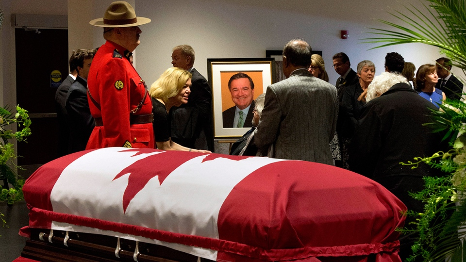 Ontario MPP Christine Elliott greets mourners in front of the casket of her husband, the late former federal finance minister Jim Flaherty, during visitation in Whitby, Ont., on Tuesday, April 15, 2014. (Frank Gunn / THE CANADIAN PRESS)