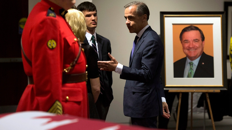Governor of the Bank of England Mark Carney chats with the family of the late former federal finance minister Jim Flaherty in front of his casket during visitation in Whitby, Ont., on Tuesday, April 15, 2014. (Frank Gunn / THE CANADIAN PRESS)