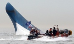South Korean coast guard officers try to rescue passengers from a ferry sinking in the water off the southern coast near Jindo, south of Seoul, South Korea, Wednesday, April 16, 2014. (Yonhap)