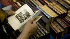 A woman flips through an antique book during in Madrid on Friday, Sept. 12, 2008.