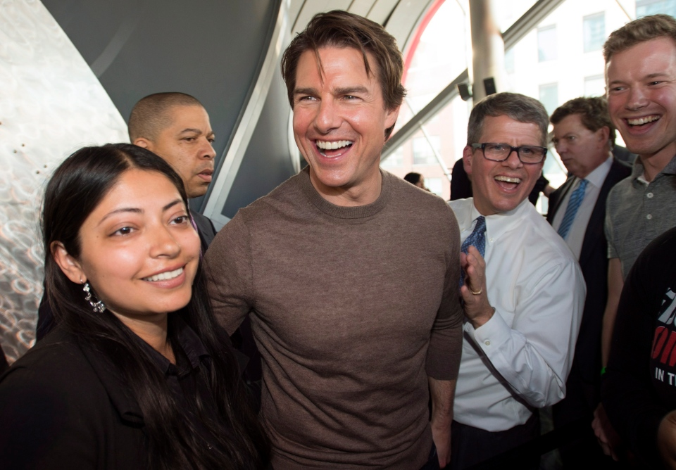 Tom Cruise laughs while posing with fans at the premiere of his new film 'Edge of Tomorrow' in Toronto on Thursday, May 29, 2014. (Darren Calabrese / THE CANADIAN PRESS)
