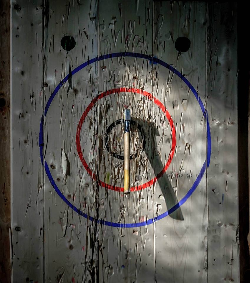 Competitors are awarded points based on where axes land on a wooden bullseye. (Nick Kelleher / UBER Events & Promotions)