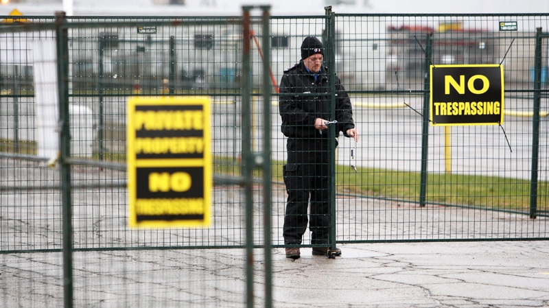 A guard locks a security fence surrounding the locomotive-maker Electro-Motive facility in anticipation of a work stoppage in London, Ont., Sunday, January 1, 2012. (Dave Chidley / THE CANADIAN PRESS)