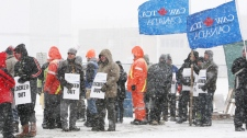 Locked-out workers and supporters picket at the locomotive-maker Electro-Motive facility in London, Ont., Monday, Jan. 2, 2012. (Dave Chidley / THE CANADIAN PRESS)