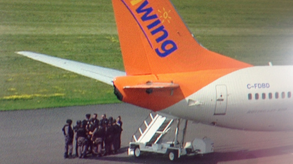 Police officers gather next to Sunwing flight 772 on the tarmac of Toronto's Pearson Airport on Friday, July 25, 2014. (Jeff Long / CTV Toronto)