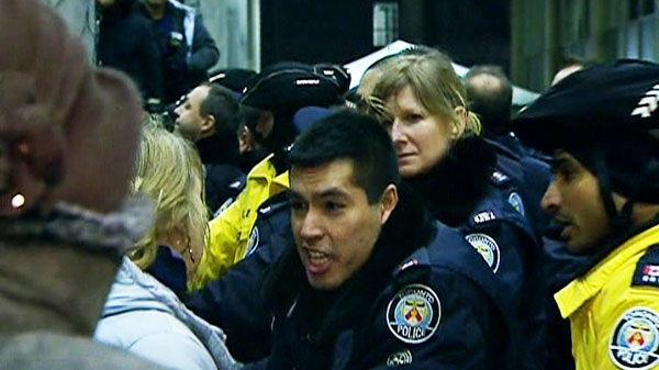 An officer speaks to protesters outside of Toronto City Hall after hundreds surrounded the building to protest the 2012 budget.