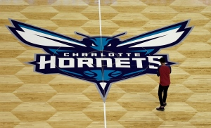 A photographer takes photos of the Charlotte Hornets logo during a news conference to unveil the design for their home court in Charlotte, N.C., on Thursday, June 26, 2014. (AP / Chuck Burton)