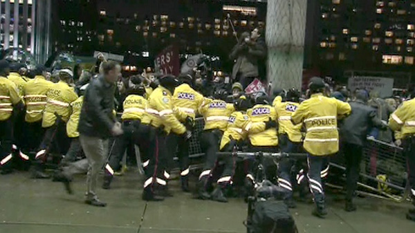 Police are seen trying to keep demonstrators from storming city hall in Toronto, Tuesday, Jan. 17, 2012.