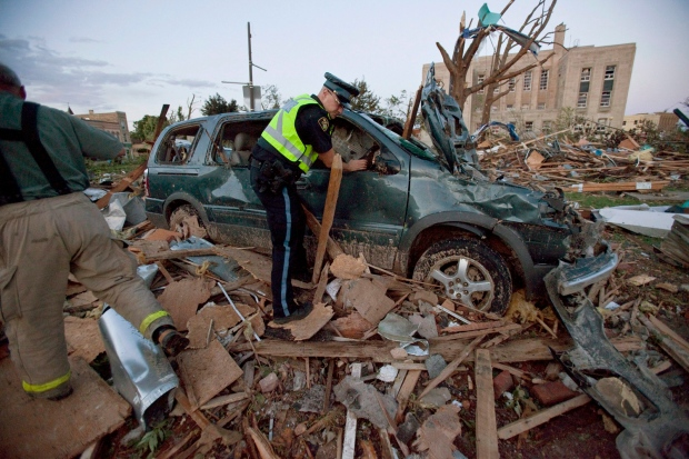 Police examine a crushed vehicle after a tornado ripped through Goderich, Ont. on Sunday, August 21, 2011. (Geoff Robins / The Canadian Press)