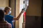 In this photo taken on Friday, Aug. 29, 2014, a health worker measures a patient's temperature at the Connaught Hospital, which has suffered the loss of medical workers in the past from the Ebola virus, in Freetown, Sierra Leone. (AP Photo/Michael Duff)