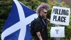 Chris McAleese holds a Saltire flag as he walks past Bannockburn Polling Station in Scotland, Thursday, Sept. 18, 2014. (AP / Andrew Milligan)
