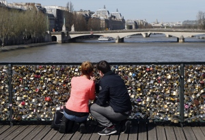 A couple hang a love padlock on the steel bar of the Pont des Arts in Paris in this undated image. (AFP / Patrick Kovarik)