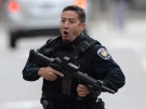An Ottawa police officer runs with his weapon drawn in Ottawa on Wednesday Oct.22, 2014.Police are expanding a security perimeter in the heart of the national capital after a gunman opened fire and wounded a soldier at the National War Memorial before injuring a security guard on Parliament Hill, where he was reportedly shot dead by Parliament's sergeant-at-arms. (THE CANADIAN PRESS/Sean Kilpatrick)