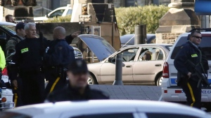A car with its windows broken sits in front of the gates to the Parliament Buildings during an active shooter situation in Ottawa on Wednesday, Oct. 22, 2014. (Patrick Doyle / THE CANADIAN PRESS)