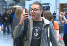 A happy iPad lover films his entrance to the Apple Store at the Eaton Centre in Toronto, Friday, March 16, 2012.