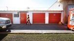 Company staff walk past storage lockers in Winnipeg, Tuesday, October 21, 2014. (John Woods / THE CANADIAN PRESS)