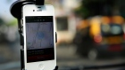 In this April 3, 2014 photo, a smartphone is mounted on the glass of an Uber car in Mumbai, India. (AP Photo/Rafiq Maqbool)