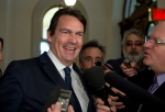 Quebec Opposition MNA Pierre Karl Peladeau smiles while surrounded by reporters as he arrives at a caucus meeting on Tuesday, Nov. 18, 2014 at the legislature in Quebec City. (Jacques Boissinot / THE CANADIAN PRESS)