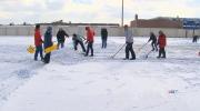 Volunteer help clear snow from stadium