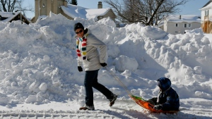 A woman pulls a child on a sled on Friday, Nov. 21, 2014, in West Seneca, N.Y. (AP / Mike Groll)