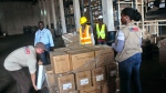 USAID workers rap Ebola virus protection equipment to be used by American, USAID, sponsored Ebola clinics across the country in Monrovia, Liberia, Wednesday, Nov. 26, 2014. (AP / Abbas Dulleh)