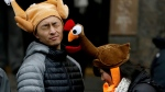 Tamari Hedani, right, hits her boyfriend, Chris Chu, both from San Francisco, with her turkey hat prior to the start of the Macy's Thanksgiving Day Parade in New York on Thursday, Nov. 27, 2014. (AP / Julio Cortez)