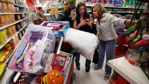 Target shoppers Kelly Foley, left, Debbie Winslow, center, and Ann Rich use a smartphone to look at a competitor's prices while shopping in South Portland, Maine shortly after midnight on Black Friday, Nov. 28, 2014. (AP / Robert F. Bukaty)