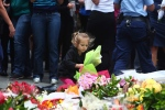 A girl lays flowers in a makeshift memorial near the site where a gunman held hostages for 16 hours at a popular Sydney cafe, Australia, Tuesday, Dec. 16, 2014. (AP / Steve Christo)