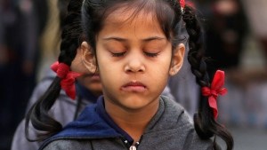 An Indian schoolgirl observes a two-minute silence for victims killed in a Taliban attack on a military-run school in Peshawar, in New Delhi, India, Wednesday, Dec. 17, 2014. (AP / Altaf Qadri)