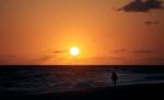 A tourist walks as the sun rises over Santa Maria beach in Havana, Cuba on Saturday, April 18, 2009. (AP Photo/Javier Galeano)