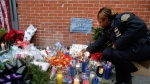 New York City police officer Marie Jean-Baptiste lights a candle at a memorial in the Bedford Stuyvesant neighborhood of the Brooklyn borough of New York, Sunday, Dec. 21, 2014 in honor of two police officers who were shot there Saturday. (AP / Mark Lennihan)