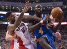 Toronto Raptors forward Amir Johnson (15) fouls New York Knicks forward Quincy Acy while battling for a rebound during first half NBA action in Toronto Sunday December 21, 2014. (Frank Gunn / THE CANADIAN PRESS)