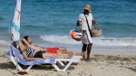 In this Dec. 19, 2014 photo, tourists sunbathe as a vendor sells kites decorated with Cuba's flag on a beach near Havana, Cuba. The easing of tourism regulations is a gamble for both the U.S. and Cuba. Obama said Wednesday that people-to-people travel was a way to 'empower the Cuban people.' At the same time, a U.S. tourism surge could funnel sorely needed cash to a tourism industry run mostly by what Obama described Friday as 'a regime that represses its people.' (AP/Desmond Boylan)