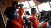 Crew of Indonesian Air Force C-130 airplane of the 31st Air Squadron scan the horizon during a search operation for the missing AirAsia flight 8501 jetliner over the waters of Karimata Strait in Indonesia, Monday, Dec. 29, 2014. (AP / Dita Alangkara)