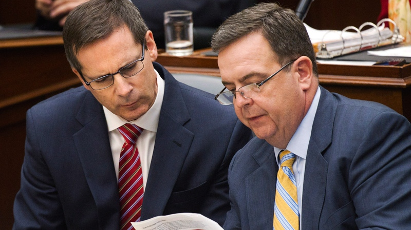 Ontario Premier Dalton McGuinty, left, and Ontario Finance Minister Dwight Duncan, right, over look a document during before the 2012 provincial budget vote at Queen's Park in Toronto on Tuesday, April 24, 2012. (Nathan Denette / THE CANADIAN PRESS)