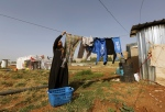 A Syrian refugee hangs laundry at a refugee camp in the eastern Lebanese town of Majdal Anjar, Lebanon, in this June 19, 2014 file photo. (AP / Bilal Hussein)