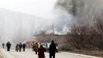 Residents pass by burning houses in Mariupol, Ukraine, Saturday, Jan. 24, 2015. (AP / Sergey Vaganov)