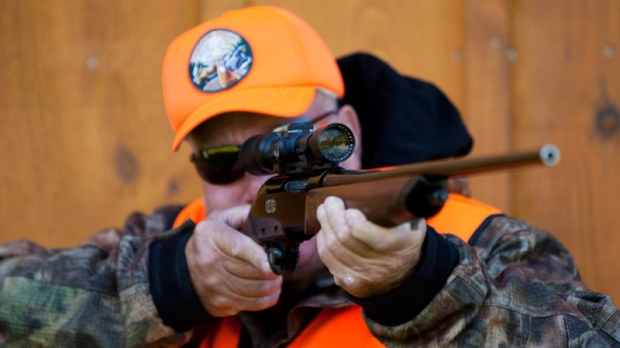 A rifle owner checks the sight of his rifle at a hunting camp property in rural Ontario west of Ottawa on Wednesday, Sept. 15, 2010. (Sean Kilpatrick / THE CANADIAN PRESS)