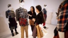 A Uniqlo worker, left, shows a journalist its latest collection during a press conference in Shanghai, China, Wednesday, Aug. 28, 2013. (AP / Eugene Hoshiko)