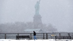 A man strolls on a walking path at Liberty State Park, with the Statue of Liberty in the distance, Monday, Jan. 26, 2015, in Jersey City, N.J. (AP / Julio Cortez)