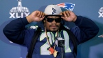 Marshawn Lynch of the Seattle Seahawks adjusts his cap during an interview ahead of NFL Super Bowl XLIX football game in Phoenix, Ariz., on Thursday, Jan. 29, 2015. (AP Photo/Matt York)