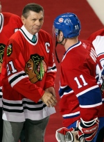 In this Jan. 8, 2008, file photo, Montreal Canadiens captain Saku Koivu (11) talks with Chicago Blackhawks great Stan Mikita during a pregame ceremony in Montreal. (AP / The Canadian Press, Paul Chiasson)