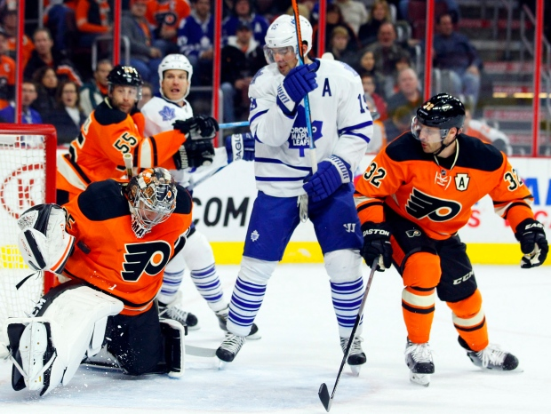 Philadelphia Flyers goalie Steve Mason, left, stops the puck under his right arm as Toronto Maple Leafs' Joffery Lupul, center, and the Flyers Mark Streit, right, look on in the first period of an NHL hockey game on Jan. 31, 2015, in Philadelphia. (Tom Mihalek / AP Photo )