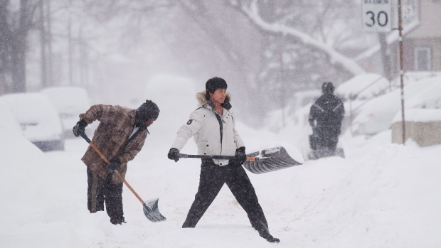 People clear snow from their sidewalks and streets after a large amount of snow fell in Toronto on Monday, Feb. 2, 2015. (Nathan Denette / THE CANADIAN PRESS)