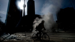 Stream rises from the street as a cyclist makes their way around Toronto on Friday, February 13, 2015. (Nathan Denette/THE CANADIAN PRESS)