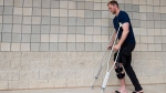 Toronto Blue Jays outfielder Michael Saunders, left, leaves the clubhouse on crutches at baseball spring training in Dunedin, Fla., on Thursday, Feb. 26, 2015. The 28-year-old Canadian was shagging balls Wednesday morning at the club's training complex when he stepped on a sprinkler head indentation and injured his knee. (Nathan Denette / THE CANADIAN PRESS)